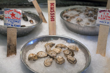 merchant: Fresh Whole Oysters Clams Mussels Shellfish in Shell on Ice for Sale in Fresh Seafood Market Stock Photo