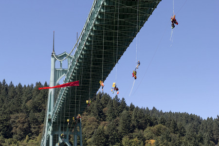 activists: PORTLAND, OREGON - JULY 29, 2015: Greenpeace USA activists rappelled off St Johns Bridge over Willamette River in Portland Oregon in protest and preventing the Shell Oil Icebreaker Vessel Fennica from leaving for oil drilling in the Arctic Editorial