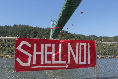 activists: PORTLAND, OREGON - JULY 29, 2015: Greenpeace USA activists rappelled off St Johns Bridge over Willamette River in Portland Oregon in protest and preventing the Shell Oil Icebreaker Vessel from leaving for oil drilling in the Arctic with red banner sign on