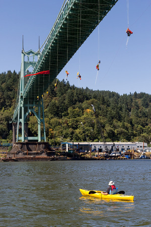 preventing: PORTLAND, OREGON - JULY 29, 2015: Greenpeace USA activists rappelled off St Johns Bridge in Portland Oregon in protest and preventing the Shell Oil Icebreaker Vessel from leaving for oil drilling in the Arctic with one kayaktivist on Willamette River