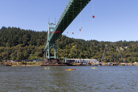 preventing: PORTLAND, OREGON - JULY 29, 2015: Greenpeace USA activists rappelled off St Johns Bridge in Portland Oregon in protest and preventing the Shell Oil Icebreaker Vessel from leaving for oil drilling in the Arctic with kayaktivists on the Willamette River