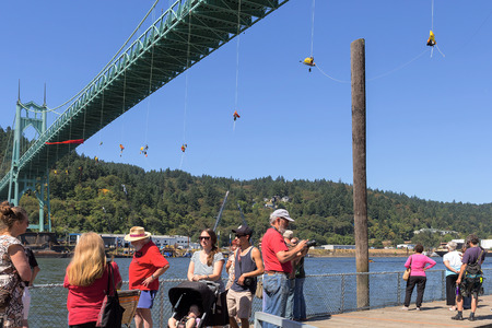 rappel: PORTLAND, OREGON - JULY 29, 2015: Greenpeace USA activists rappelled off St Johns Bridgein Portland Oregon in protest blocking the Shell Oil Icebreaker Vessel leaving for oil drilling in the Arctic with spectators and supporters on pier Editorial