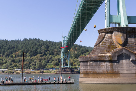 greenpeace: PORTLAND, OREGON - JULY 29, 2015: Greenpeace USA activists rappelled off St Johns Bridgein Portland Oregon in protest blocking the Shell Oil Icebreaker Vessel from leaving for oil drilling in the Arctic with spectators and supporters on pier Editorial