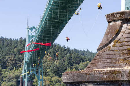 greenpeace: PORTLAND, OREGON - JULY 29, 2015: Greenpeace USA activists rappelled off St Johns Bridge in Portland Oregon in protest blocking Shell Oil Icebreaker Vessel from leaving for oil drilling in the Arctic Editorial