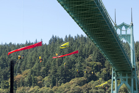 greenpeace: PORTLAND, OREGON - JULY 29, 2015: Greenpeace USA activists rappelled off St Johns Bridgein Portland Oregon in protest blocking the Shell Oil Icebreaker Vessel leaving for oil drilling in the Arctic with signs and banners