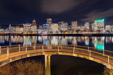 eastbank: Portland Oregon downtown city skyline from pedestrian bridge along Willamette River at night Stock Photo