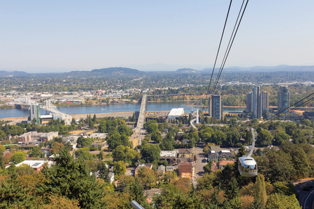 waterfront: Portland Aerial Tram Public Transportation above Portland Oregon cityscape with Tilikum Crossing and Ross ISland Bridge over Willamette River Stock Photo