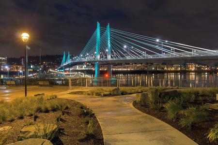 willamette: Tilikum Crossing Bridge Over Willamette River by the Waterfront Walkway in Portland Oregon at Night