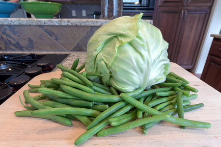 white headed: Head of Cabbage and String Beans on Chopping Board by Kitchen Cooking Stove Top