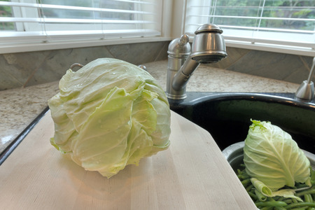 ingredients tap: Head of Cabbage on Chopping Board over Kitchen Sink Stock Photo