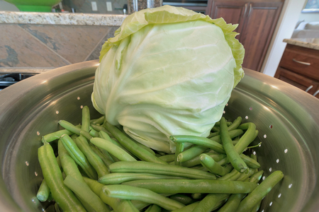 white headed: Head of Cabbage and String Beans in Colander closeup macro Stock Photo