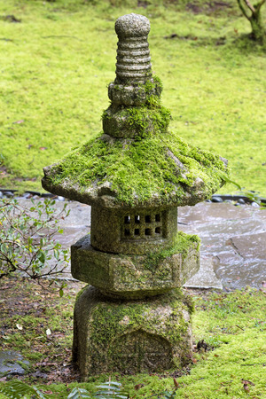 hardscape: Old Stone Lantern covered in green moss at Japanese Garden Stock Photo