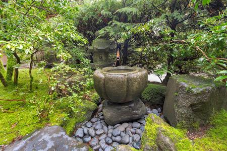 bamboo fountain: Tsukubai Water Fountain with Bamboo Kakeki and Stone Lantern at Japanese Garden in Spring Stock Photo