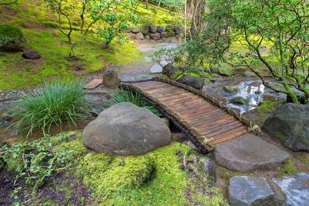 Bambú del puente del pie sobre el arroyo en primavera en el jardín japonés