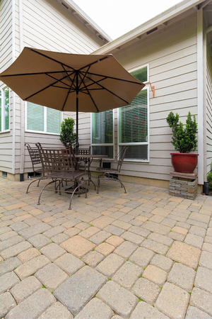 Garden Backyard with brick paver patio and furniture with table chairs and umbrella