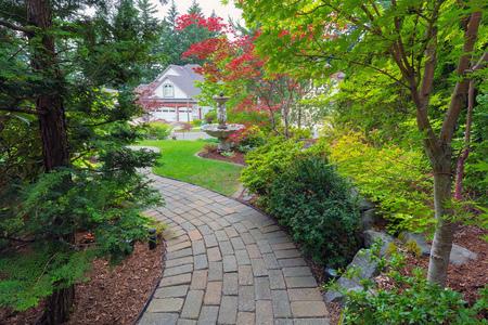 Garden bakstenen bestrating pad in de voortuin met fontein planten struiken evergreen en loofbomen landschapsarchitectuur Stockfoto