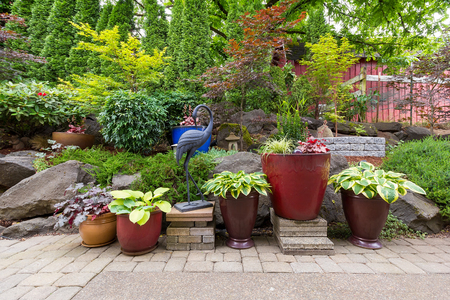 hardscape: House Garden Backyard with hardscape and softscape with plants trees pavers stones colorful pots containers in landscaping Stock Photo