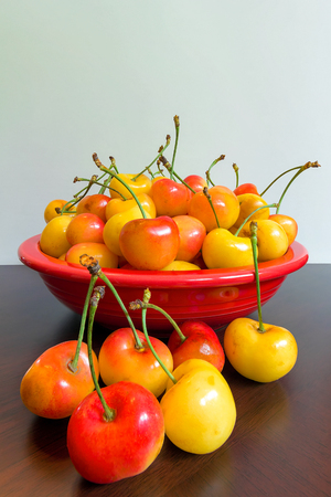 Pile of Rainier Cherries in a red bowl sitting on a wooden table