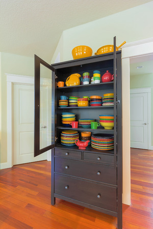 cherry hardwood: Cupboard with colorful stoneware dinnerware in home with cherry hardwood floor