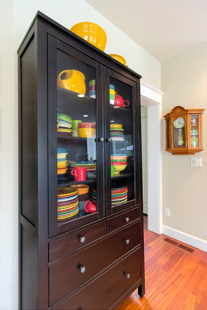 wood molding: Wood China Cupboard with colorful dinnerware and Oak Pendulum Clock interior home