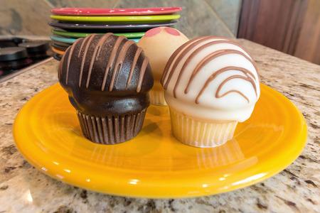 Cupcakes sweet dessert on yellow plate sitting on granite kitchen countertop Stock Photo