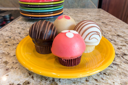 Cupcakes sweet dessert on yellow plate sitting on granite kitchen countertop closeup macro