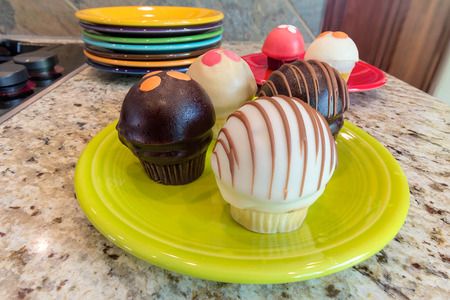 granite countertop: Cupcakes sweet dessert on lime green plate sitting on granite kitchen countertop closeup macro
