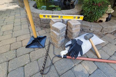 Stone straatstenen voor achtertuin patio vijver hardscape met tuinaanleg gereedschap handschoenen niveau rubberen hamer zand grind sabotage Stockfoto
