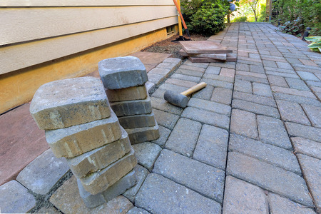 hardscape: Stone Pavers and tiles for side yard patio hardscape with garden landscaping tools rubber mallet sand gravel tamper