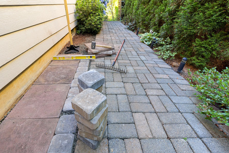 hardscape: Stone Pavers and tiles for side yard patio hardscape with garden landscaping tools rubber mallet sand gravel tamper level rake