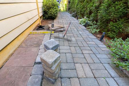 Stone straatstenen en tegels voor zijtuin terras hardscape met tuinaanleg gereedschap rubberen hamer zand grind sabotage niveau rake