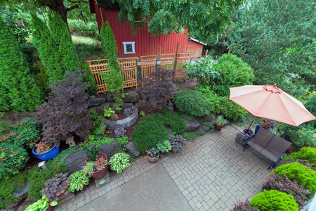 Backyard garden landscaping with paver bricks patio hardscape trees potted plants shrubs pond rocks furniture and red barn Stock Photo