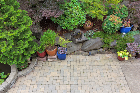 Backyard garden landscaping with paver bricks patio hardscape trees potted plants shrubs pond rocks and decor Stock Photo