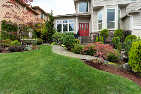Frontyard garden of house with water fountain green grass lawn paver brick path trees and shrubs landscaping