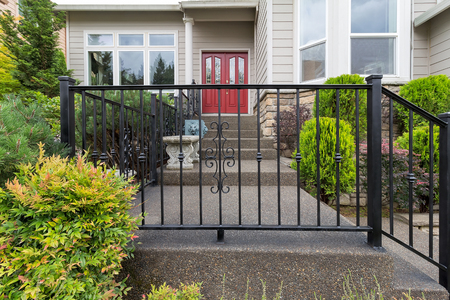 House front entrance with wrought iron railings on stairs with plants landscaping Zdjęcie Seryjne