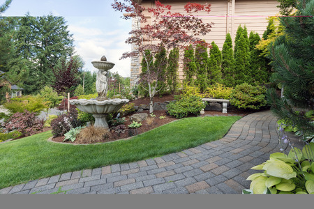 House manicured frontyard garden with water fountain stone bench green lawn plants trees shrubs and brick paver walkway path