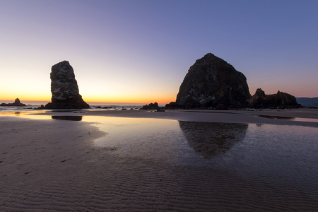 Haystack Rock and the Needle at Cannon Beach along Oregon Coast at sunset Stock Photo