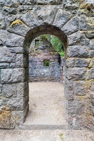 Abandoned stone castle house arch doorway at Wildwood Trail in Forest Park Portland Oregon