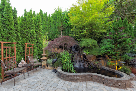 Backyard Garden landscaping with waterfall pond trees plants trellis decor patio furniture brick pavers Stock Photo - 60832430