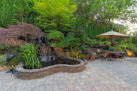 Dvorek zahrada krajinářství s vodopád rybník stromy rostlin trellis dekor nábytek cihlové dlaždice patio hardscape Reklamní fotografie