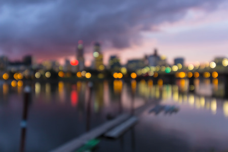 willamette: Portland Oregon city downtown waterfront skyline along Willamette River after sunset at dusk out of focus blurred bokeh lights