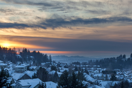 Happy Valley Oregon suburban neighborhood homes covered in snow during sunset