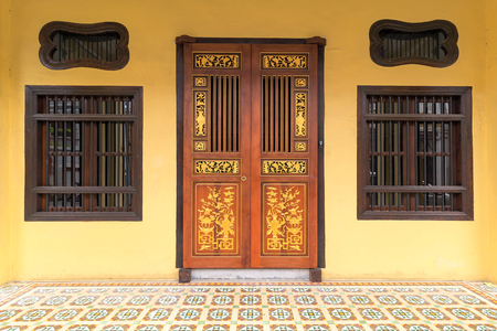 Peranakan typical style windows and ornate entrance doors an floor tiles in Penang Malaysia