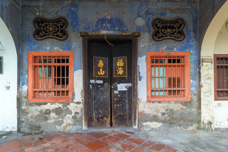 old doors: Old Run-Down Peranakan style home exterior with Chinese text Longevity Mountain and Properous Sea on wooden doors entrance Stock Photo