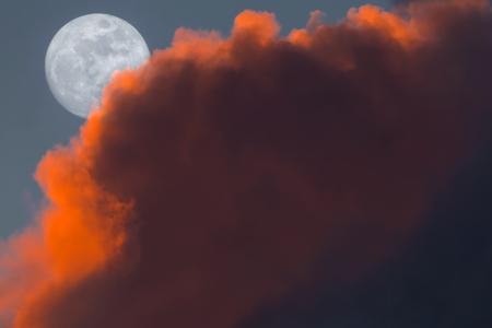 alpenglow: Full Snow Moon Rise peeking behind pink clouds during sunset