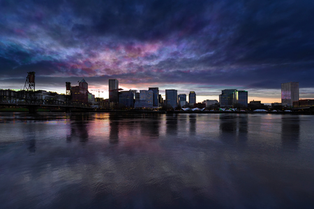 waterfront property: Portland Oregon downtown city skyline from Eastbank Esplanade along Willamette River waterfront during cloudy twilight evening Stock Photo