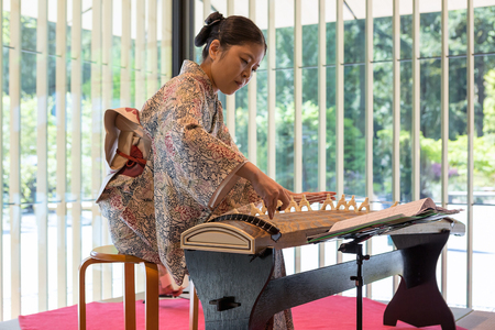 PORTLAND, OREGON - May 6, 2017: Koto Harpist Eri Muroi playing at the Cultural Village in Portland Japanese Garden. Koto harp is a thirteen-string plucked zither, part of the Gagaku court ensemble for over one thousand years, gradually becoming popular am