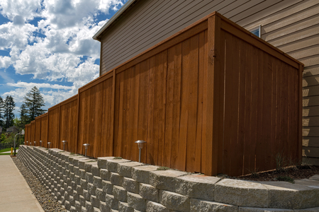 Wood fence cement stack stone blocks retaining wall and landscaping lighting Archivio Fotografico