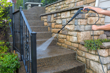frontyard: Washing the house front entrance stair steps and stone walls with pressure power washer Stock Photo