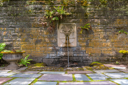 Renaissance Garden with Lion Head water fountain on a stone block wall with stone steps and planter Stock Photo